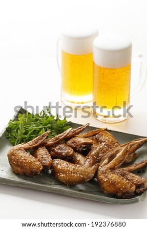 Two glasses of beer behind a plate of cooked chicken wings with a parsley garnish. - stock photo