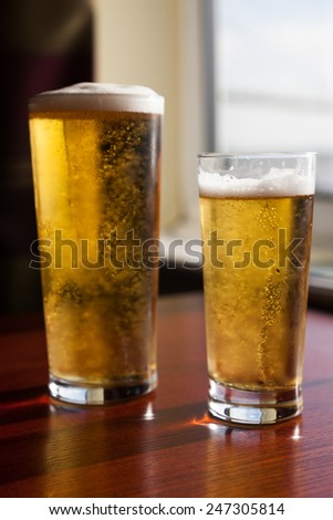 Two glasses of beer by the window - stock photo