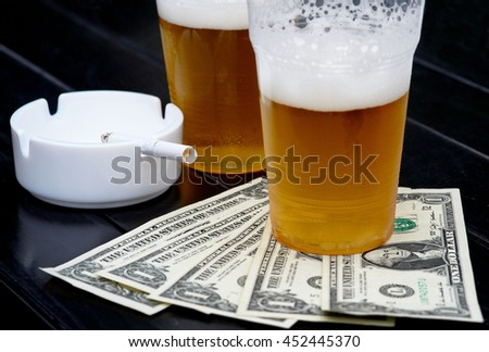 Two glasses of beer, fan-shaped dollars and ash tray with cigarette