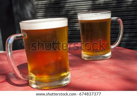 Two glasses of beer on a red table cloth outside.  There are drips of water running down the glasses