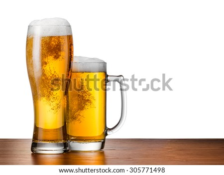 Two glasses of beer on a wooden table - stock photo