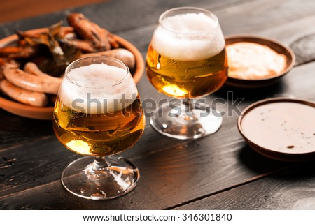 Two glasses of beer on the black table with snacks - stock photo