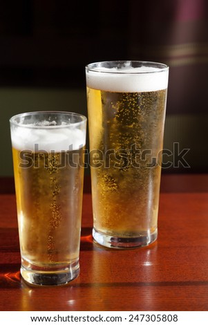 Two glasses of beer on the wooden table - stock photo
