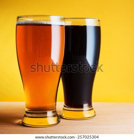 Two glasses of beer on yellow background