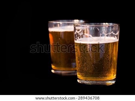 Two glasses of beer, one after another , isolated on black background - stock photo
