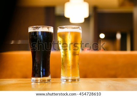 Two glasses of beer over a dark background - stock photo