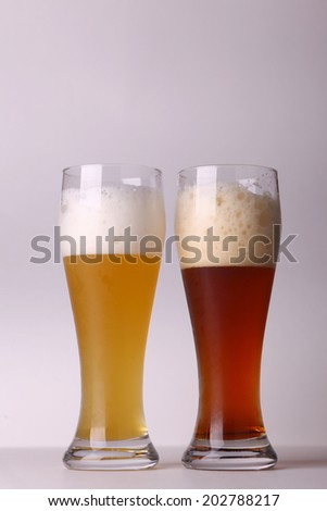 Two glasses of beer over a grey background