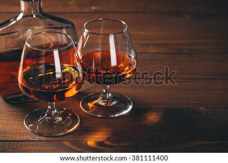 Two glasses of brandy or cognac and bottle on the wooden table. - stock photo