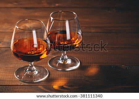 Two glasses of brandy or cognac on the wooden table.