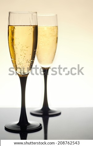 Two glasses of bubbly champagne or sparkling wine on dark grey reflective surface. Selective focus is on the near glass. Glasses have black bases and stems. Background fades from golden tan to white.