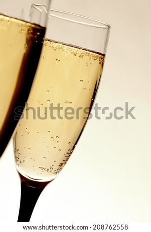 Two glasses of bubbly champagne or sparkling wine. Selective focus on the second glass. Vertical image is tilted to the right. Background is a neutral almond color that is brighter toward the bottom. - stock photo