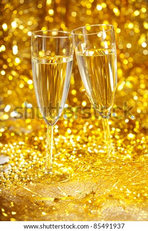 Two glasses of champagne against the gleaming background - stock photo
