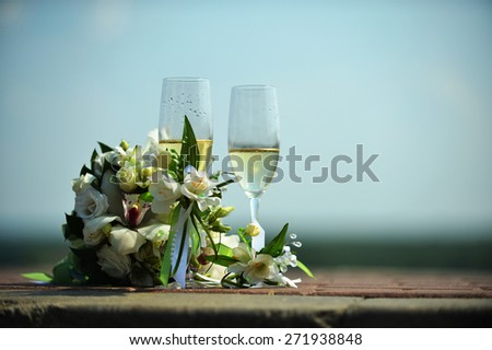 two glasses of champagne against the sky - stock photo
