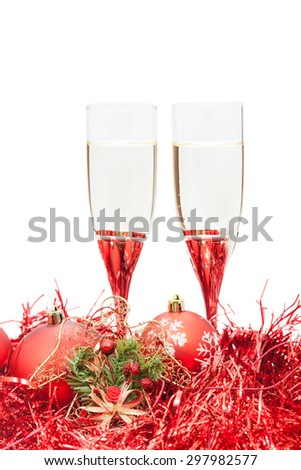 two glasses of champagne and angel figure at red Christmas balls and tinsel isolated on white background