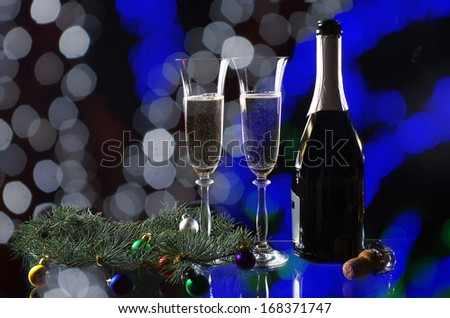 Two glasses of champagne and bottle on the festive background