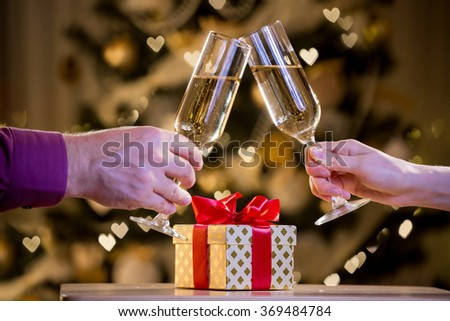 Two glasses of champagne and gift box with red bow. Background with blurred lights, bokeh of heart. Man and woman celebrating  - stock photo