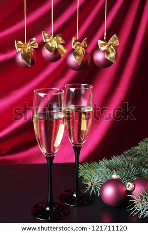 Two glasses of champagne and new year decoration against purple drapery - stock photo