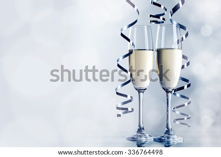 Two glasses of champagne and ribbons on light bokeh background - stock photo