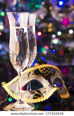 Two glasses of champagne and venetian mask on shiny background