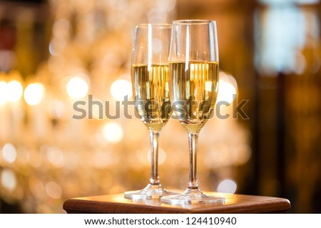 Two glasses of champagne in a fine dining restaurant, a large chandelier is in Background - stock photo