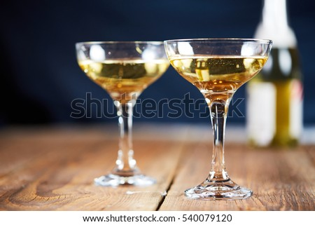 Two glasses of champagne in front of bottle on wooden table