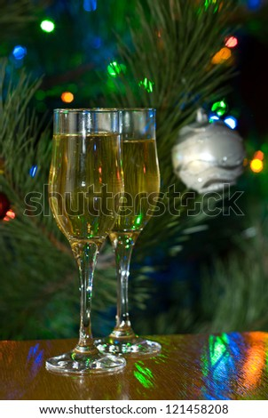 Two glasses of champagne in front of lighted christmas tree