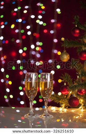 Two glasses of champagne near beautiful christmas tree