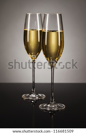 two glasses of champagne on a mirror with a spot light background
