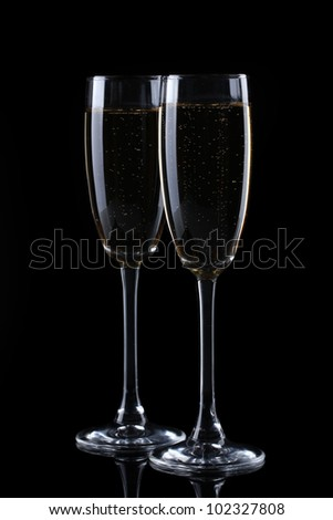 two glasses of champagne on black background