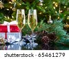 two glasses of champagne on green christmas background and gifts - stock photo
