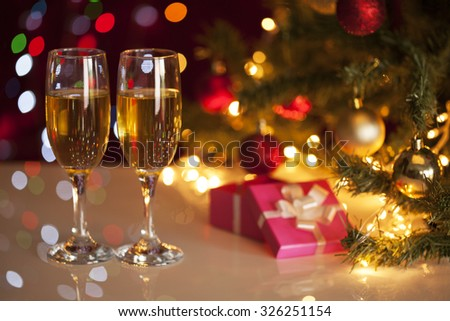 Two glasses of champagne on green christmas tree and gifts