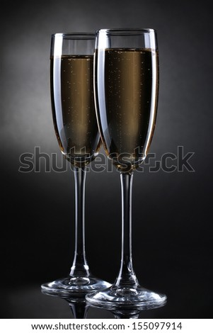 two glasses of champagne on grey background