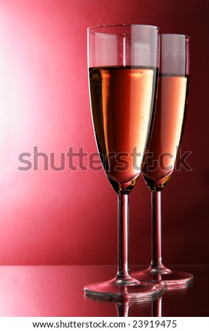 Two glasses of champagne over red background - stock photo