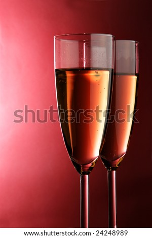 Two glasses of champagne over red background