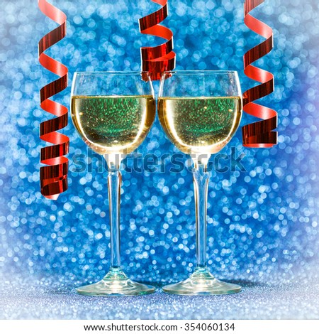 two glasses of champagne ready for christmas celebration, on blue background