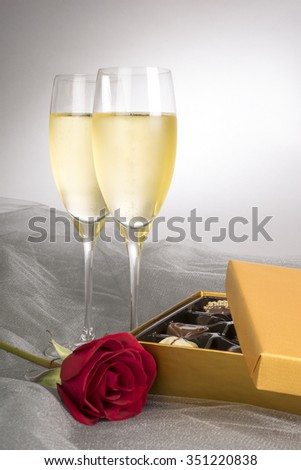 Two Glasses of Champagne, Single Red Rose and Box of Chocolates - stock photo