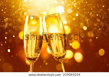 two glasses of champagne toasting against gold bokeh background - stock photo