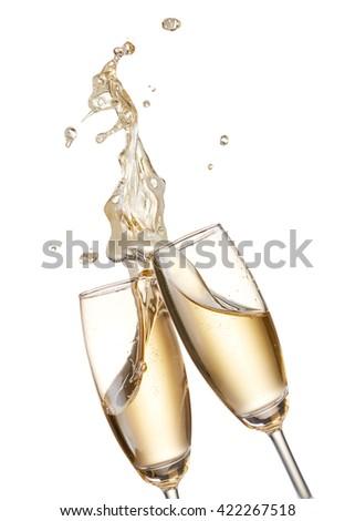 two glasses of champagne toasting creating splash - stock photo