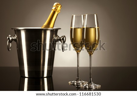 two glasses of champagne with a champagne bottle in a bucket on a mirror with spot light - stock photo
