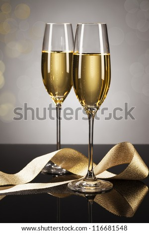 two glasses of champagne with a golden ribbon on a mirror with a spot light background - stock photo