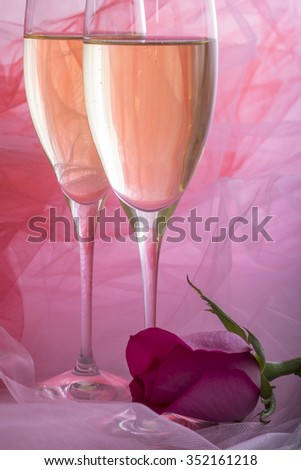Two Glasses of Champagne with Backlit Tulle Background and One Single Pink Rose - stock photo