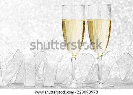 Two glasses of champagne with bow on silver background - stock photo
