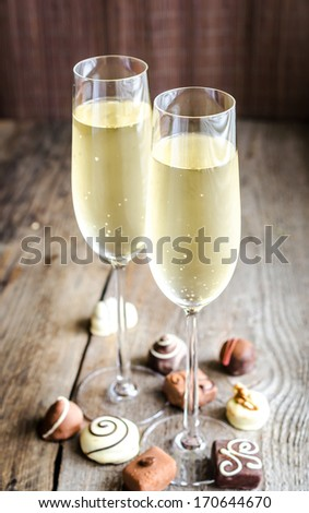 Two glasses of champagne with candies - stock photo