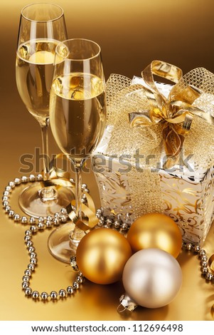 two glasses of champagne with christmas present and christmas balls - stock photo