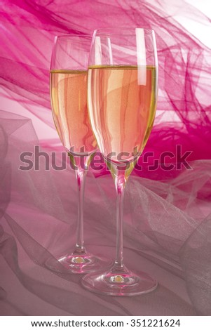 Two Glasses of Champagne with Pink and Grey Tulle Background and Backlit - stock photo