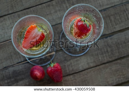 two glasses of champagne with strawberries on wooden table - stock photo