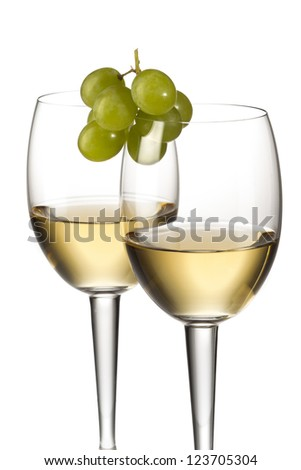 Two glasses of champagne with white grapes on top - stock photo