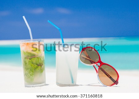 two glasses of chilled cocktail mohito pina colada and sunglasses on a sand beach - stock photo