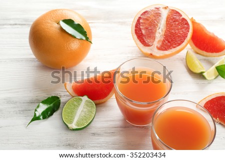 Two glasses of citrus juice and fresh fruits on light wooden background - stock photo