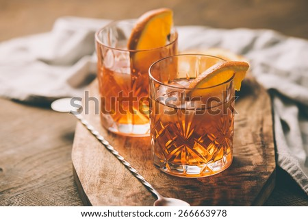 Two glasses of cocktail with orange slice. Toned image - stock photo